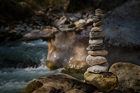 beige stacked stones near body of water at daytime
