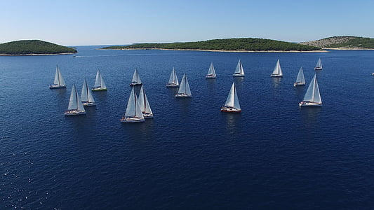 aerial view photography of white sailboats at sea surrounded by islands under clear sky during daytime