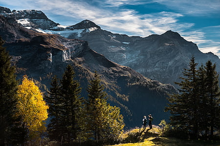 photo of two people standing near mountains