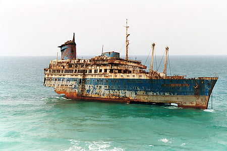 photo of blue and brown ship surrounded by body of water