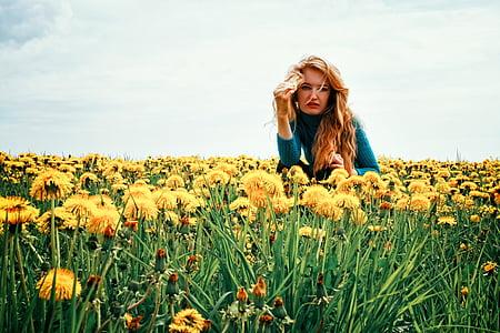 woman sitting on yellow dandelion field