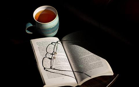 white opened book near mug with coffee
