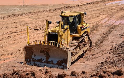 yellow heavy equipment on soil field