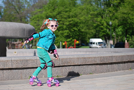 girl in blue jacket and green pants skating near fountain