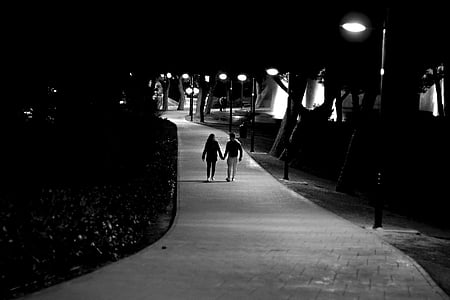 grayscale photo of male and female holding hands under light posts