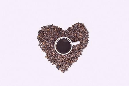 white ceramic mug on brown heart-shaped coffee beans