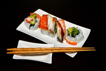 sushi on plate beside brown chopsticks