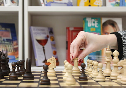 woman about to move chess rook