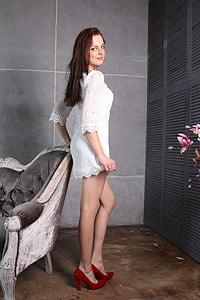 woman wearing white dress standing near couch