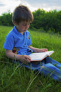 boy sitting on green grass field while reading book during daytime