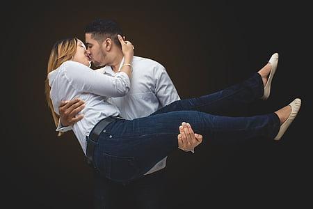 man carrying woman white kissing