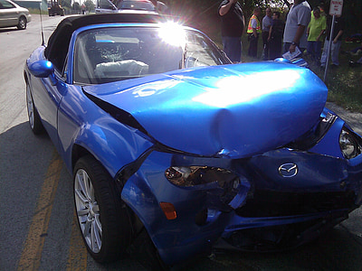 wrecked blue Mazda coupe on highway during daytime