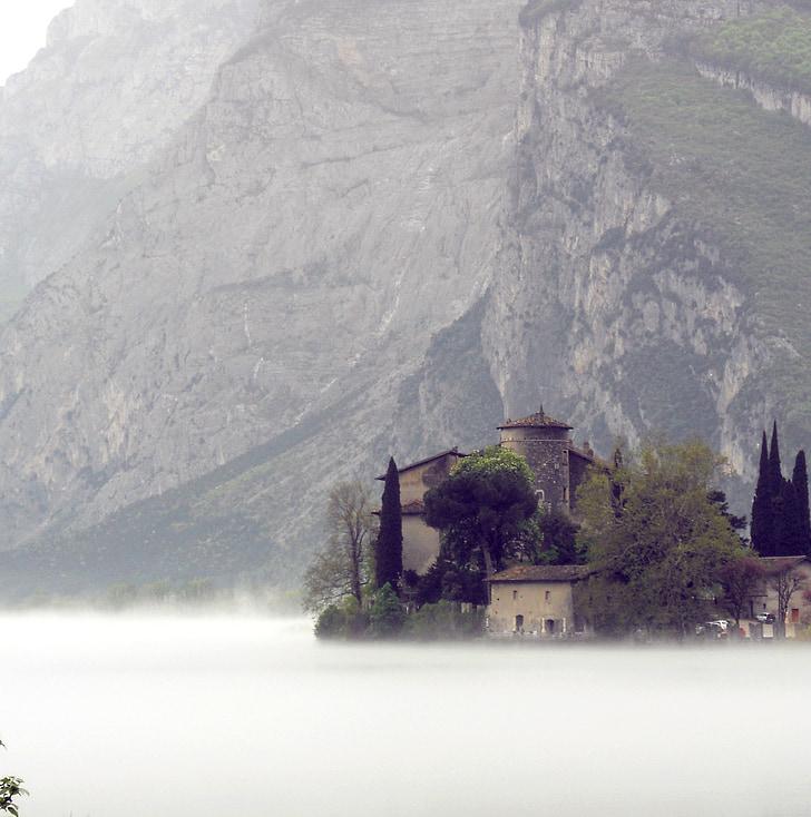 grey concrete house near mountain during fog