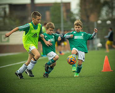 boy's playing soccer during daytime