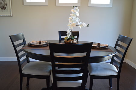 round brown wooden table with four chairs inside room