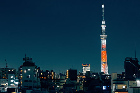 city skyline with orange and white tower at night