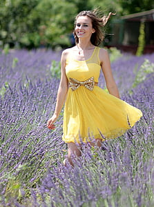 woman in dress standing on flower field