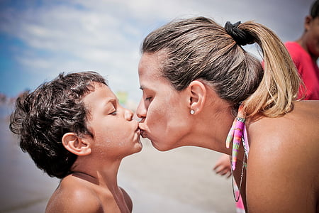 woman kissing boy in shallow focus lens