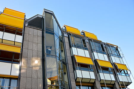 low angle of gray and yellow building undr blue sky