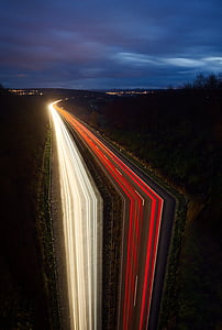 time-lapse photography of highway surrounded by trees under cloudy skies