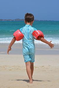 photo of boy wearing blue wet suit